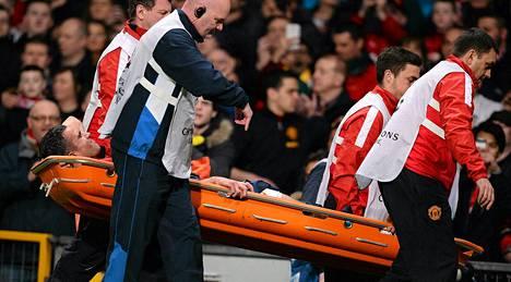 Manchester Unitedin Robin van Persie kannettiin paareilla kentältä Olympiakos-ottelussa.