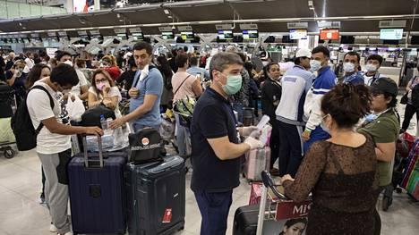 Matkailijat jonottivat Bangkokin lentokentällä viime vuoden maaliskuussa, kun Thaimaa sulki rajojaan koronaviruksen vuoksi.