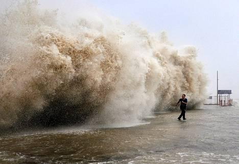 Mies juoksi pakoon hirmumyrsky Usagin nostattamaa jättiaaltoa satamalaiturilla Shantoussa Kiinassa.