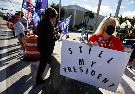 """Trump supporters on the roadside in West Palm Beach, Florida on Wednesday.  The sign reads """"Still my president""""."""