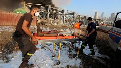Beirutin satamassa räjähti viime viikon tiistaina varasto, jossa säilöttiin ammoniumnitraattia. Haavoittunutta miestä kannettiin turvaan tapahtumapaikalta.