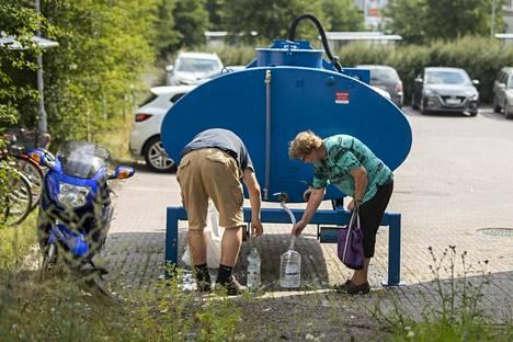 Ihmiset hakivat juomavettä Naantalin terveysaseman pihalle vedenjakeluhäiriöiden takia tuodusta vedenjakelupisteestä tiistaina.