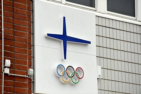 Olympiakomitean tunnus, siniristi ja olympiarenkaat, Sporttitalon seinässä Helsingissä.