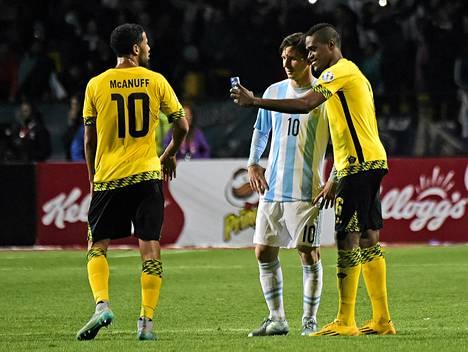 Jamaikalaishyökkäjä Deshorn Brown nappaamassa pelin jälkeen selfietä argentiinalaistähti Messin kanssa. Brownin joukkuekaveri Joel McAnuff tarkkaili tilannetta lähituntumasta.