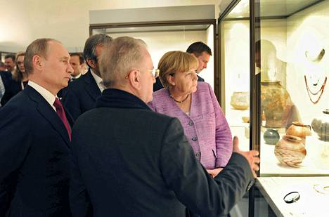 Saksan liittokansleri Angela Merkel ja Venäjän presidentti Vladimir Putin kuuntelevat Eremitaasin johtajan Mihail Pjotrovskin (selin)esittelyä pronssikautisista taide-esineistä eilen Pietarissa.