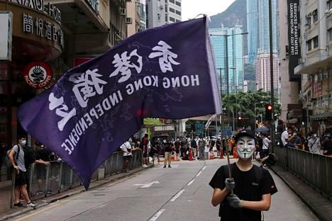 Mielenosoittaja heilutti Hongkongin itsenäistymistä kannattavaa lippua sunnuntaina.