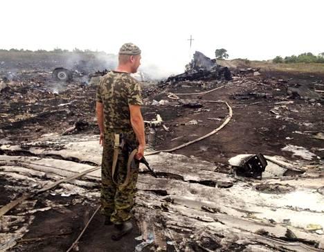 Venäjän-mielinen separatisti seisoi alas ammutun matkustajakoneen osien vieressä lähellä Donetskin aluetta torstaina.