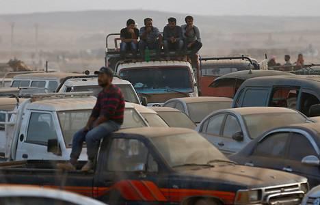 Suurin osa Kobanin alueen siviileistä on paennut taisteluja Turkin puolelle. Kuvan miehet odottelivat pääsyä Turkin puolelle rajan tuntumassa syyskuun lopulla.
