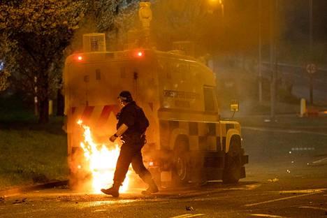 Poliisi kulki tulessa olleen poliisiauton ohi Belfastin pohjoispuolella sijaitsevassa Newtownabbeyssa lauantaina.