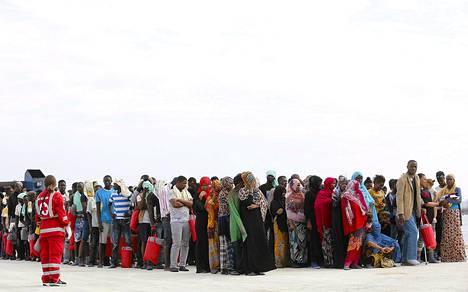Siirtolaiset odottivat laiturilla noustuaan maihin Lääkärit ilman rajoja -järjestön laivasta Italian Sisiliassa maanantaina. Laivan kyydissä oli 320 siirtolaista.