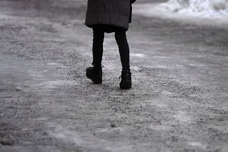 Jalankulkija käveli jäisellä mutta hiekoitetulla kadulla Helsingissä maanantaina 4. helmikuuta.