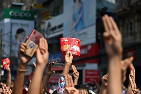 Mielenosoittajat nostivat kolme sormea merkiksi sotilasvallan vastustamisesta Yangonissa. Kylteissä toistuivat vangitun johtajan Aung San Suu Kyin ja presidentti Win Myintin kasvot.