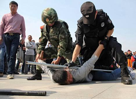 Poliisi piteli terroristia näytellyttä miestä aloillaan harjoituksessa, joka järjestettiin Yiwun asemalla Xhejiangin maakunnassa keskiviikkona.