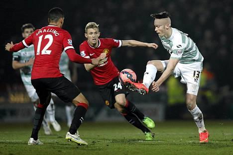 Yeovil-hyökkääjä Kieffer Moore (oik.) eteni pallon kanssa kohti Unitedin puolustusta, jossa Chris Smalling (12) ja Darren Fletcher (kesk.) yrittivät pysäyttää Moorea.