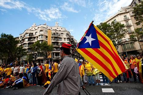 Katalonian itsenäisyyttä kannattava mies piteli lippua ihmisketjun edessä Barcelonassa syyskuussa.