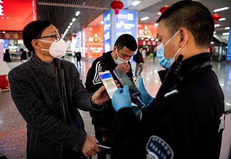 Kiinan Wenzhoussa matkustaja näytti viranomaiselle puhelimestaan QR-koodia, joka kertoo tämän terveydentilasta. Kuva on otettu helmikuun 28. päivänä.