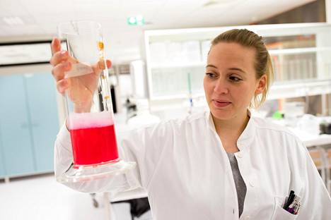 Laborantti Heta Haikonen näyttää astiaa, jossa on bioreaktorin tuottamaa vasta-ainesoluja sisältävää nestettä. Sen arvo on kymmeniätuhansia euroja.