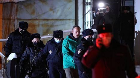 Poliisit vievät oppositiopoliitikko Aleksei Navalnyitä maanantaina oikeuden jälkeen poliisiautoon Moskovassa.