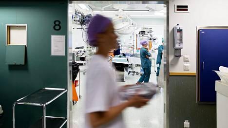 Heinäkuu on Meilahden sairaalassa vuoden kiireisin kuukausi, koska maakuntien sairaalat ovat kiinni. Kuvassa: Sairaalan hoitajat valmistelee huonetta leikkausta varten.