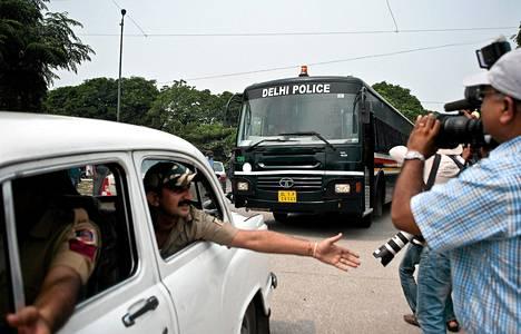 Intialainen poliisi pyytää katsojia siirtymään syrjään bussin tieltä joka kuljettaa neljää kuolemaan tuomittua joukkoraiskaukseen osallistunutta miestä.