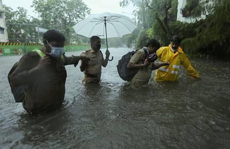 Asukkaita autettiin ylittämään Tauktae-syklonin nostattaman tulvaveden peittämää katua Mumbaissa maanantaina.