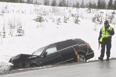 Poliisi tutki kolariautoa tien sivussa.