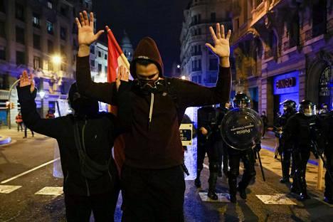 Pablo Hasélia puolustavat mielenosoittajat nostivat kädet ilmaan poliisien lähestyessä Barcelonassa viime sunnuntaina.