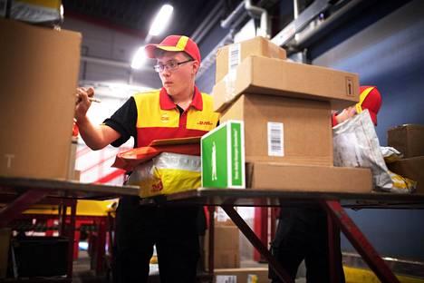 Kuriirit Ernest Lara (edessä) ja Manu Rönkkö lajittelivat eri kaupunginosiin lähteviä paketteja DHL:n Vantaan-toimipisteellä perjantaina.