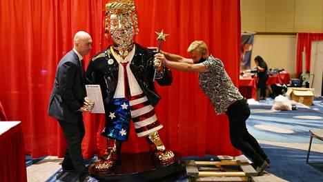 Taiteilija Tommy Zegan (oik.) siirsi Donald Trumpia esittävää patsasta CPAC-konferenssin pitopaikalla Floridan Orlandossa lauantaina.