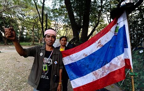 Vallatun ministeriön edustalla loukkaantui torstain ammuskelussa yksi. Vichao Kunchanakan (vas.) esittelee siteenä käytettyä lippua.