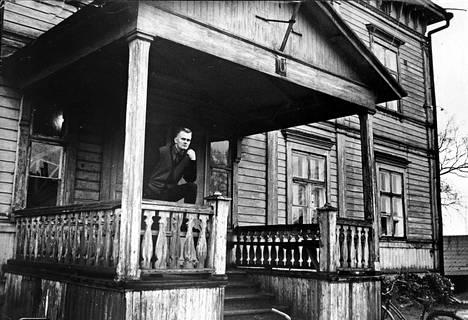 Ylivartija Kauppinen kummitustalo numero kymmenen terassilla. Hän asuu talon suurimmassa huoneistossa, keittiö ja yksi huone, neliöitä vähän yli 30. Kauppisella on viisihenkinen perhe.