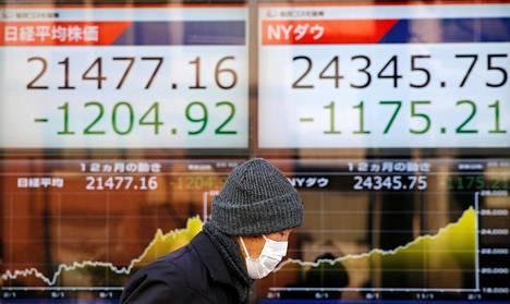 Mies käveli Nikkei ja Dow Jones -indeksejä seuraavan valotaulun ohi Tokiossa tiistaiaamuna.