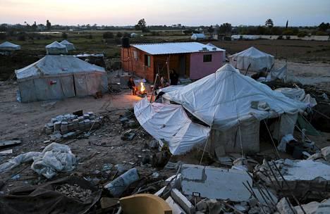 Palestiinalaiset istuivat tilapäismajoituksessaan lähellä kotinsa raunioita. Silminnäkijöiden mukaan koti tuhoutui Israelin armeijan tykistötulessa Gazassa kesällä 2014.