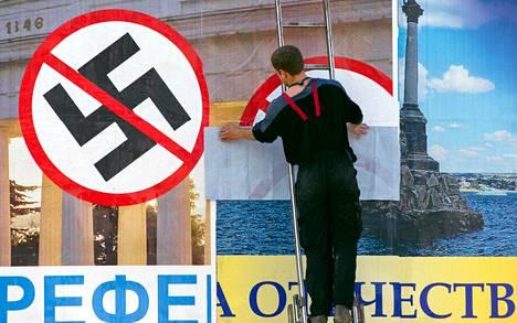 Mies kiinnitti maanantaina julistetta toisen päälle Sevastopolissa Krimin niemimaalla. Peittyvä juliste kehottaa ihmisiä äänestämään fasismia vastaan sunnuntain kansanäänestyksessä.