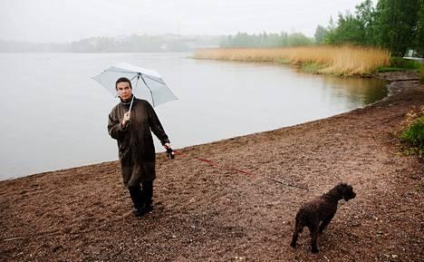 """Tihkusateessa Töölönlahti ei ole hehkeimmillään, mutta Nana Uitto ja hänen Rafu-koiransa kiertävät sitä uskollisesti säässä kuin säässä. Kuvan maisemaan haikailevassa meriuimalassa Uittoa kiinnostaa eniten mahdollinen uusi kahvila. """"Olen monta kertaa miettinyt, miksei rannoilla ole edes kesäaikaan enemmän kahviloita"""", Uitto miettii."""