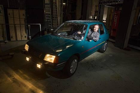 Paavo Westerberg poseeraa Mahdolliset maailmat -näytelmän autossa. Näytelmässä auto on paikka, jossa lapsitähti Antti Tähtinen saa hetken huoahtaa ennen aviokriisikotiin palaamista.