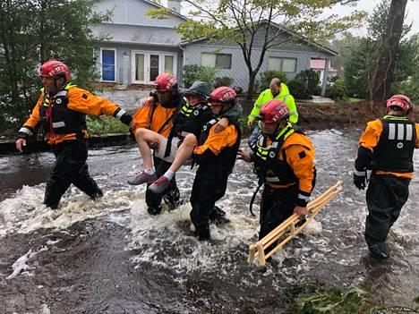 New Yorkista paikalle hälytetyt pelastustyöntekijät kantoivat evakuoitavaa asukasta River Bendissä Pohjois-Carolinassa perjantaina.