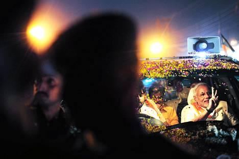 Intian vaaleja johtava Narendra Modi (oik.) tervehtii kannattajiaan kukkien terälehdin kuorrutetusta autostaan Varanasissa perjantaina.