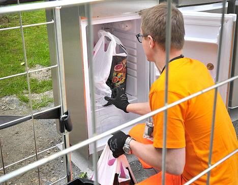 Avustaja Timo Keränen kantoi palvelukeskuksessa asuvan Eila Fribergin ostokset jääkaapille asti.