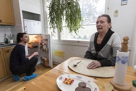 Elisa Ojalainen ottaa jääkaapista ateriapalvelun toimittamaa ruokaa ja lämmittää sen Annelille.