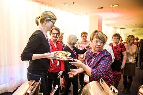 Riitta Holm (oik.) kokosi kymmeniä jouluruoka-annoksia senioreiden joululounaalla. Muut vapaaehtoiset kuljettivat annokset pöytiin.