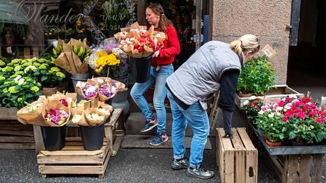 Kukkakauppias Charlotta Widén punaisessa puserossa asetteli tarjontaansa esille Korkeavuorenkadulla yhdessä Hanna Huttusen kanssa.