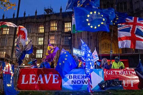 Brexitin kannattajia ja vastustajia oli kyltteineen ja lippuineen rinta rinnan parlamenttitalon edessä maanantai-iltana.