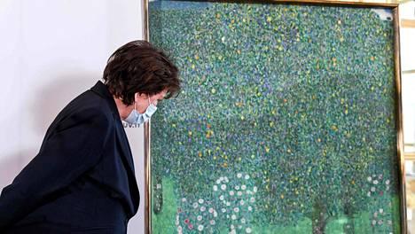 Ranskan kulttuuriministeri Roselyne Bachelot Gustav Klimtin Ruusupensaita puiden alla -teoksen (1905) äärellä. Ranska palauttaa teoksen sen vuonna 1938 menettäneen ja myöhemmin holokaustin uhriksi joutuneen Nora Stiasnyn perheelle.