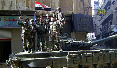 Syyrian armeijan sotilaat näyttivät voitonmerkkiä Jouret al-Shiahin kaupunginosassa Homsissa viime viikolla. Kuva on Syyrian virallisen uutistoimiston Sanan välittämä.