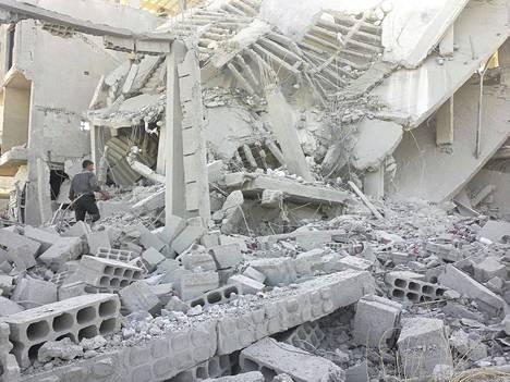 Asukkaat etsivät ruumiita Syyrian armeijan ilmapommituksissa tuhoutuneen rakennuksen raunioista Erbeenissä Damaskoksen lähellä maanantaina.