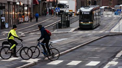 Pyöräilijöitä ja raitiovaunu Hämeentiellä. Katu on suunniteltu erityisesti joukkoliikenteen, jalankulkijoiden ja pyöräilijöiden tarpeisiin.