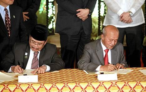 Kapinallisjohtaja Mohagher Iqbal (vas.) ja rauhanneuvottelija Dato Tengku Abdul Ghafar Tengku Mohamed allekirjoittavat rauhansopimuksen Manilassa.