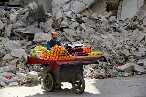 Hedelmäkauppias odotti asiakkaita tuhoutuneen rakennuksen vieressä Syyrian Aleppossa maanantaina.