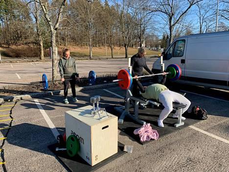 Sami Muhosen Liikkuvat puntit -yritys kuljettaa treenivälineitä ulkotiloihin. Tässä vanhemmat kuntoilevat jalkapallokentän laidalla lasten potkiessa palloa.